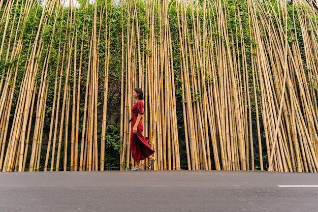 이국적인 나라. 대나무 배경 위에 포즈를 취하는 동안 반 위치에 서 있는 예쁜 갈색 머리 여성 사람