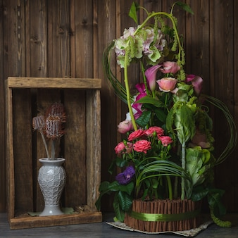 Exotic flower bouquet inside wooden basket wrapped with green ribbon.