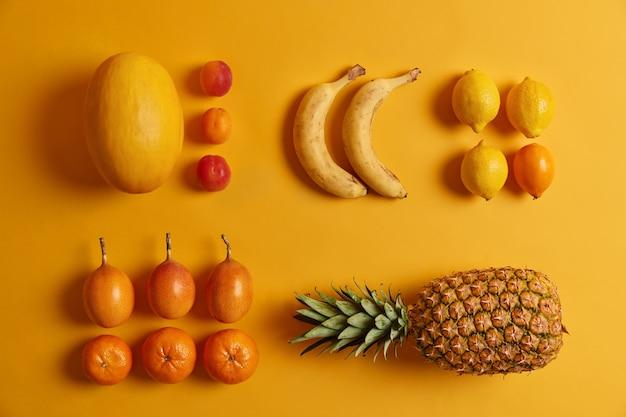 Экзотические свежие спелые сочные фрукты на желтом фоне. персики, лимоны, апельсины, цумкват, ананас, банан для приготовления вкусного салата. концепция питания. витамины, питательные вещества, освежение. здоровое питание