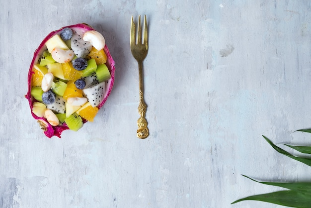Exotic fruit salad served in half a dragon fruit on palm leaves on stone background, copy space. flat lay