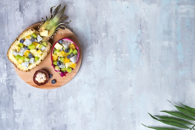 Exotic fruit salad served in half a dragon fruit and pineapple on round wooden plate on stone background, copy space. top view