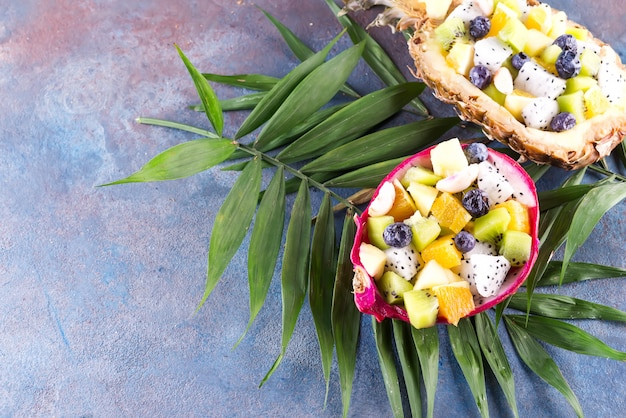 Exotic fruit salad served in half a dragon fruit and pineapple with palm leaf on stone background, copy space. top view