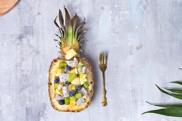 Exotic fruit salad served in half a pineapple on palm leaves on stone background, copy space. flat lay