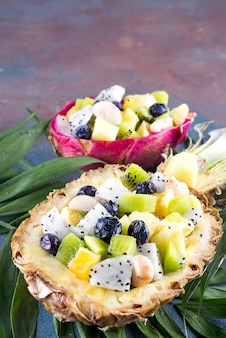 Exotic fruit salad served in half a pineapple on palm leaves on stone background