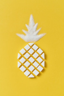Exotic fruits composition creative pineapple handmade from rafined anf granulated sweet sugar on a yellow wall with copy space. flat lay.