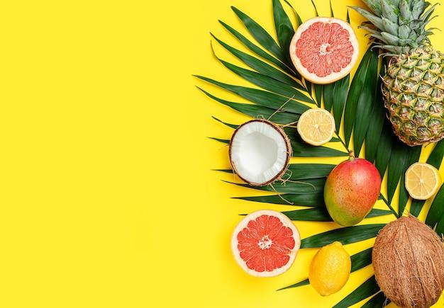 활기찬 노란색 배경에 이국적인 과일 구성입니다. 평면 위치, 복사 공간. 여름 개념.