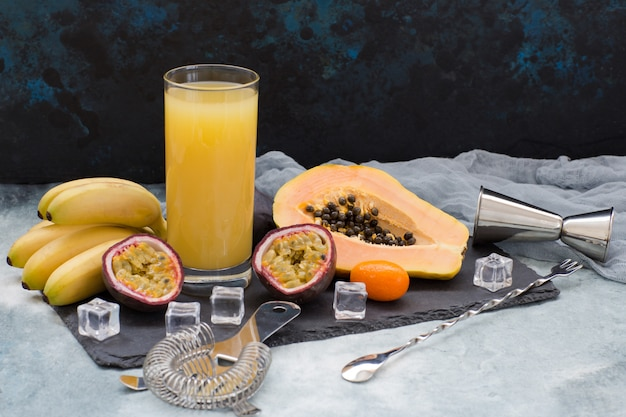 Exotic fruits, ice cubes, items for making alcoholic cocktails and a glass of juice