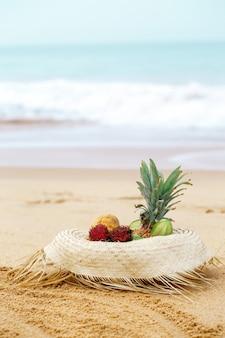 바다 근처 밀짚 모자에 이국적인 과일
