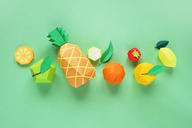 緑の表面に紙で作られたエキゾチックなフルーツ
