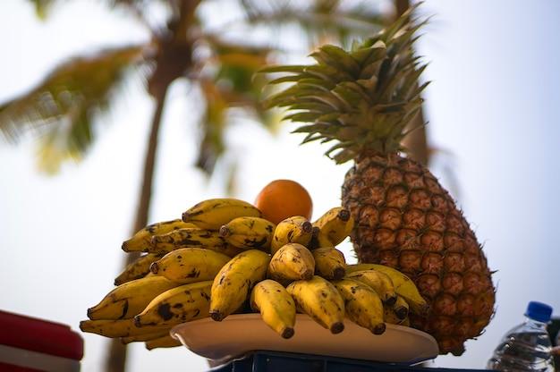 Экзотические фрукты на фоне пальм и берега. пикник в тропической стране на пляже.