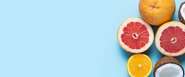 파란색 바탕에 이국적인 과일입니다. 코코넛, 오렌지, 자몽