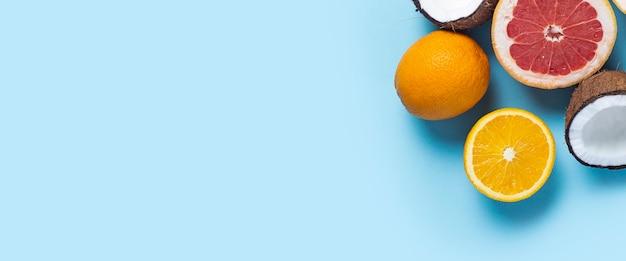 Экзотические фрукты на синем фоне. кокос, апельсин, грейпфрут