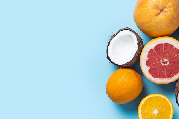 Экзотические фрукты на синем розовом фоне. кокос, апельсин, грейпфрут.