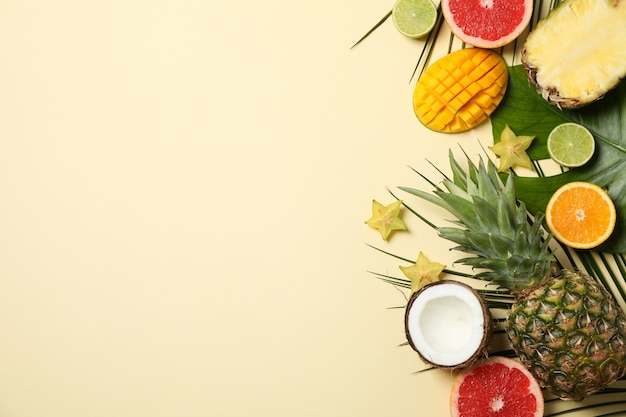 Exotic fruits and palm leaves on beige background, space for text