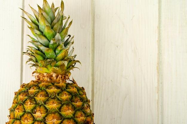 エキゾチックなフルーツ。木製の背景に熟した甘い熟したパイナップル。スタジオ写真
