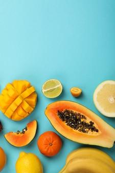 Экзотические фрукты на синем фоне, место для текста.