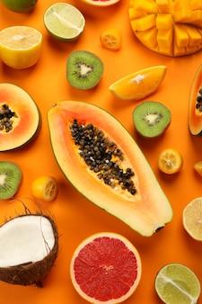 オレンジ色の背景、上面図に設定されたエキゾチックなフルーツ。