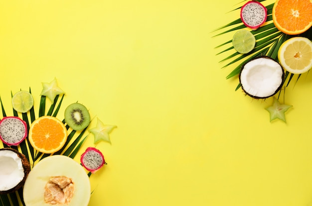 Exotic fruits and tropical palm leaves  - papaya, mango, pineapple, banana, carambola, dragon fruit, kiwi, lemon, orange, melon, coconut, lime.