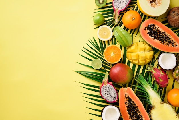 Exotic fruits and tropical palm leaves - papaya, mango, pineapple, banana, carambola, dragon fruit, kiwi, lemon, orange, melon, coconut, lime.