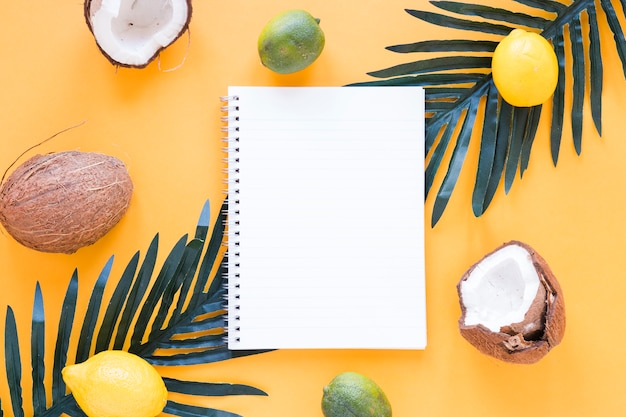 Exotic fruits with blank notebook on table