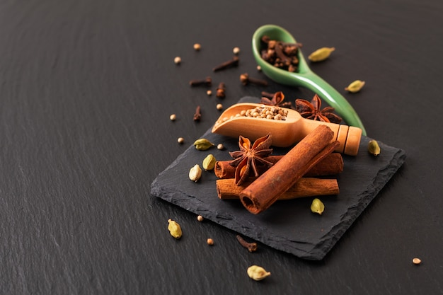 Exotic herbal food concept mix of the organic spices cinnamon stick, cardamom pods
