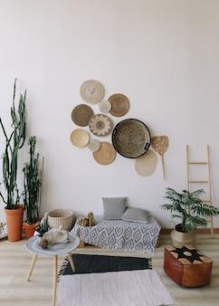 壁に自由奔放に生きるスタイルの装飾的なわらのプレートのリビングルームのエキゾチックなインテリア
