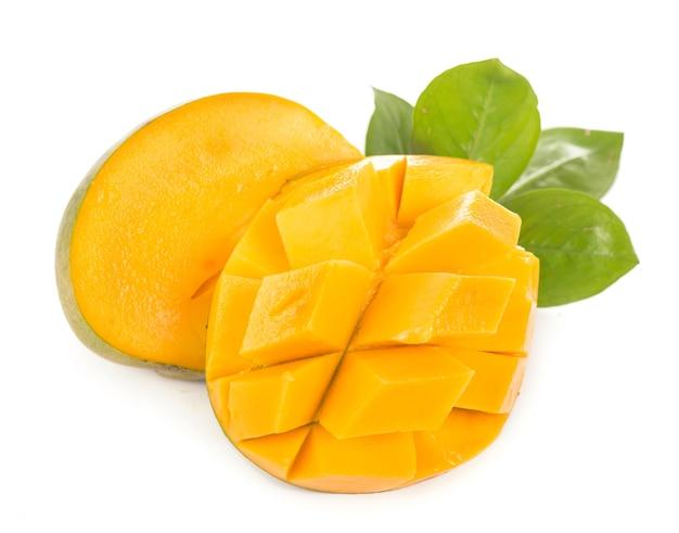 エキゾチックなジューシーなマンゴーの果実と白い表面に分離された葉