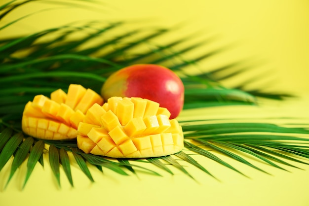 Exotic mango fruit over tropical green palm leaves on yellow background. pop art design, creative summer concept. banner