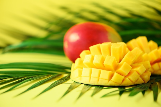 Exotic mango fruit over tropical green palm leaves on yellow background. pop art design, creative summer concept.