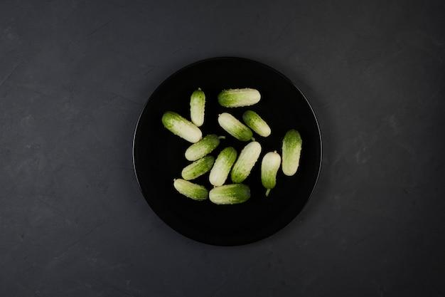 Piccolo bianco 품종의 이국적인 미니 오이가 검은 접시에 있습니다.