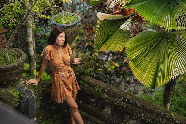 이국적인 자연. 생각에 깊이 빠져 있고 걷는 동안 이국적인 식물을 즐기는 기뻐하는 갈색 머리 여성