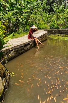 이국적인 자연. 주황색 물고기가 있는 물을 바라보면서 모자를 만지는 기쁘게 된 갈색 머리 소녀
