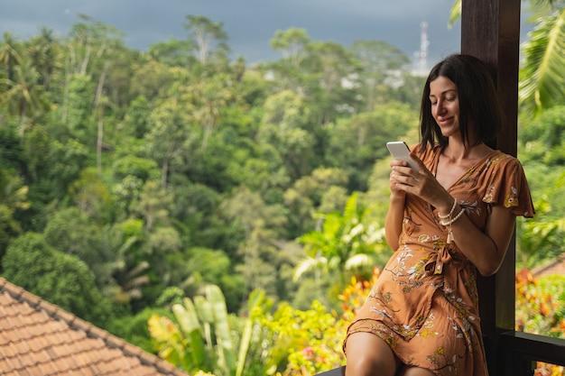 이국적인 자연. 온라인으로 좋은 소식을 읽는 동안 얼굴에 미소를 유지하는 예쁜 갈색 머리 소녀
