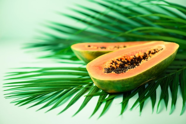 Экзотические фрукты папайи на тропических зеленых пальмовых листьев. сырая веганская еда.