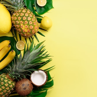 Exotic pineapples, coconuts, banana, melon, lemon, palm and monstera leaves on yellow, violet background