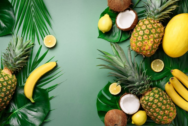 Exotic pineapples, coconuts, banana, melon, lemon, tropical palm and monstera leaves on green.