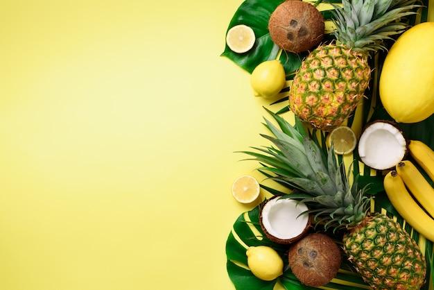 Экзотические ананасы, спелые кокосы, банан, дыня, лимон, тропическая пальма и зеленые листья монстера