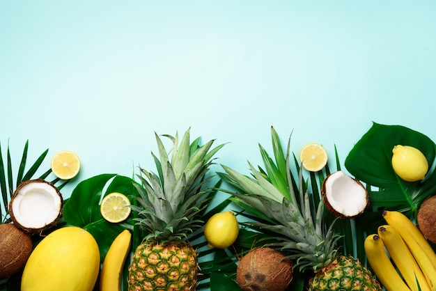 Exotic pineapples, ripe coconuts, banana, melon, lemon, tropical palm and green monstera leaves