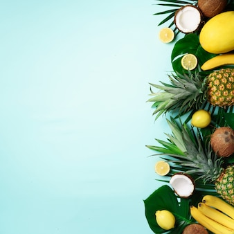 Exotic pineapples, ripe coconuts, banana, melon, lemon, tropical palm and monstera leaves on blue background