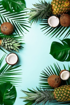 Exotic pineapples, ripe coconuts, tropical palm and green monstera leaves