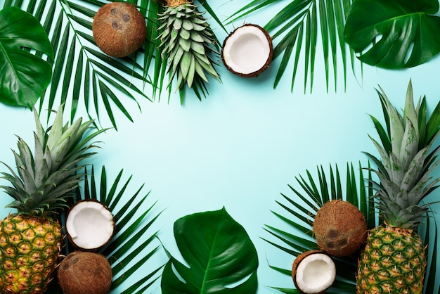 Exotic pineapples, ripe coconuts, tropical palm and green monstera leaves.