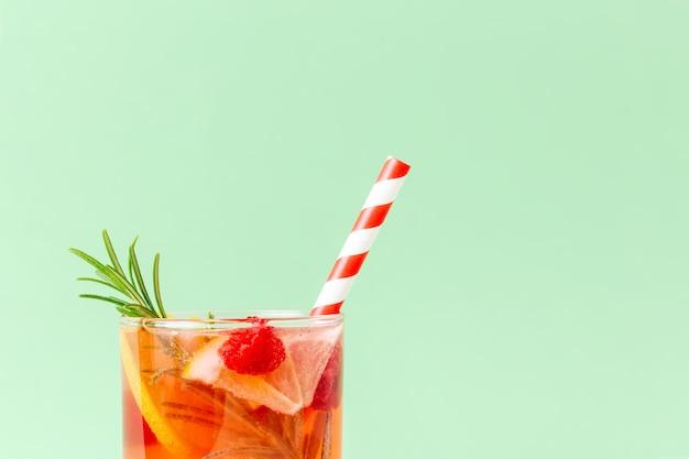 Экзотический красный холодный напиток с лимоном, розмарином и малиной с двухцветной бумажной соломкой на мятном фоне