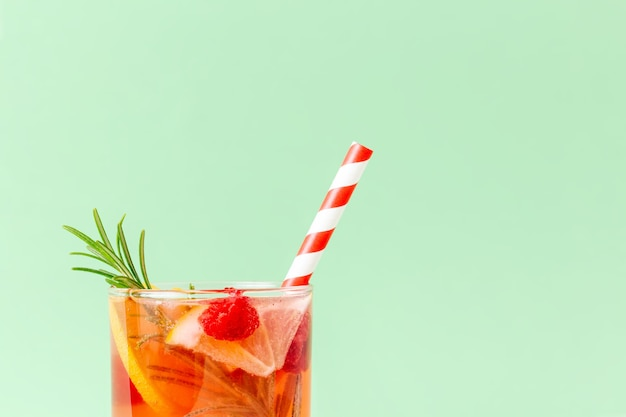 Exotic red cold drink with lemon rosemary and raspberry with bicolor paper straw on mint background
