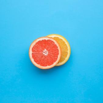 青い背景にエキゾチックな赤オレンジスライス。食べ物や飲み物の概念のアイデア