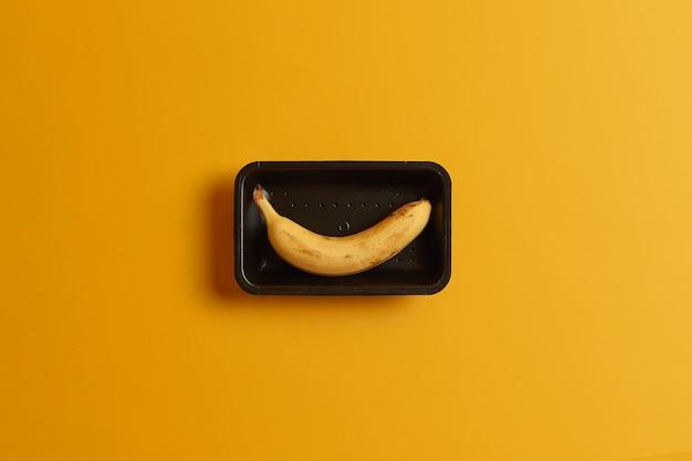 エキゾチックな熟したバナナの果実は、黄色の背景で隔離のスーパーマーケットでの販売のためのトレイに詰められました。おいしくてヘルシーなおやつ。ダイエット有機食品の概念。夏のビタミンダイエット。横ショット