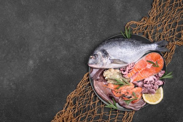 Экзотическое блюдо из морепродуктов в тарелке и рыболовная сеть