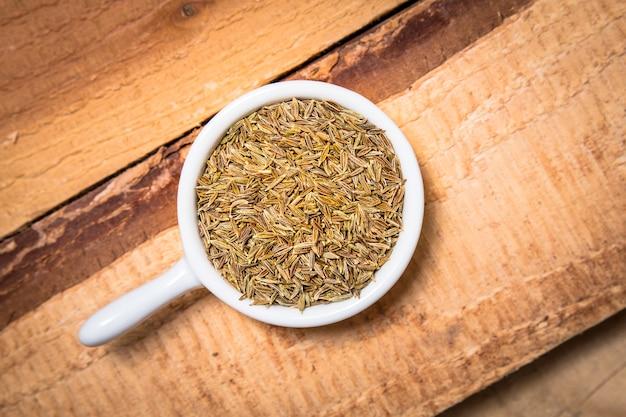 Концепция экзотических специй органические семена тмина в белом чашке
