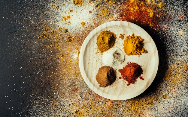 Exotic spices on round wooden plate