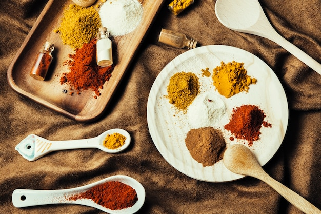 Exotic spices with plate and board on cloth