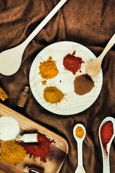 Exotic spices with plate and spoons on cloth
